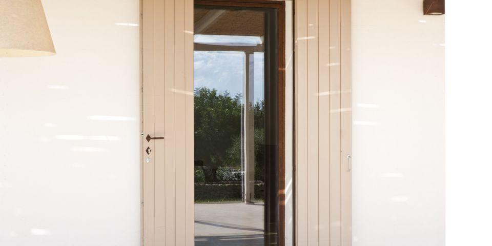 porta finestra in cor-ten con scuri in legno